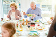 Portrait of happy family enjoying dinner together sitting round festive table with delicious dishes, focus two grandparents, copy space