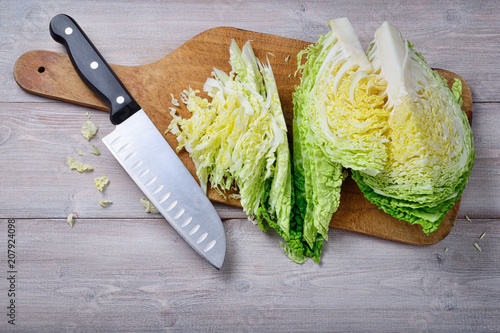 Savoy cabbage, cutting board and knife on wooden background. Top view