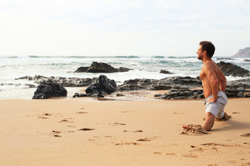 Man doing an exercise on the beach against the ocean