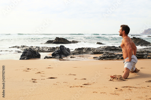 Man doing an exercise on the beach against the ocean