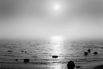 Beautiful landscape at seaside with stones in water and visible through fog sun and its reflection. Black and white