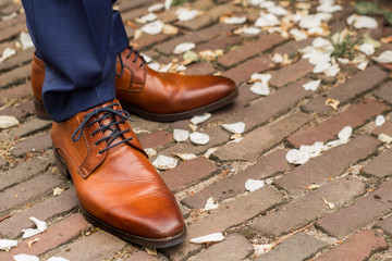 Brown leather groom shoes in white rose leaves