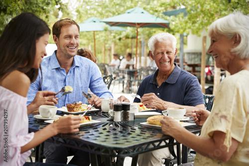 Leinwanddruck Bild Senior Parents With Adult Children Enjoying Meal At Outdoor Cafe