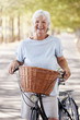 Leinwanddruck Bild - Portrait Of Smiling Senior Woman Cycling On Country Road