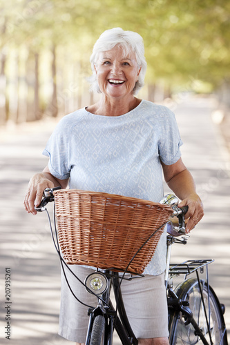 Leinwanddruck Bild Portrait Of Smiling Senior Woman Cycling On Country Road