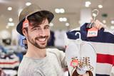 Glücklicher junger Mann beim Shopping - 207935456
