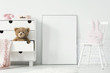 Mockup of empty poster between cabinet with teddy bear and white chair in kid's interior. Real photo. Paste your poster here