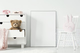 Mockup of empty poster between cabinet with teddy bear and white chair in kid's interior. Real photo. Paste your poster here - 207937009