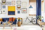 Real photo of a retro bike standing next to the window in bright living room interior with navy blue settee, wooden cupboard, orange painting and posters - 207937206