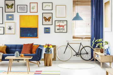 Real photo of a retro bike standing next to the window in bright living room interior with navy blue settee, wooden cupboard, orange painting and posters