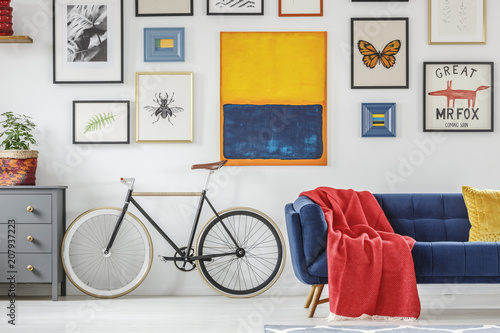 Foto Murales Bright red blanket on a navy blue settee standing next to a vintage bicycle against white wall with a gallery of posters in living room interior. Real photo