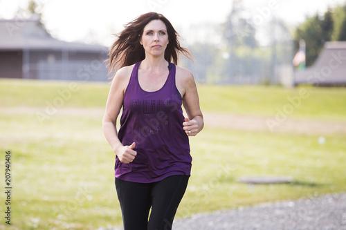 Plexiglas Fitness Healthy mature woman running outside