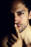 bel homme faisant le geste du silence sur un fond noir - 207948813