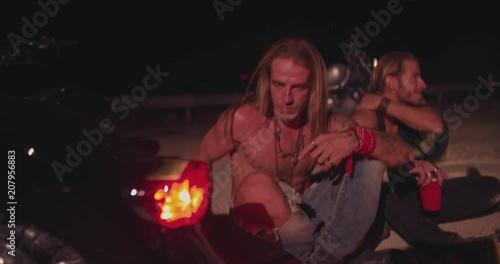 Rebel men with long hair and motorcycles drinking at night