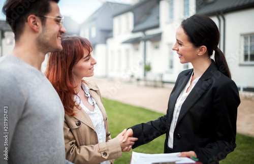 Leinwandbild Motiv Real estate agent shaking hands with customers after buying new house in residential area
