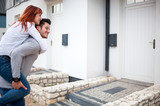 Man carrying wife on his back in front of their new home, happy couple after buying real estate - 207959070