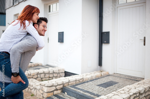 Man carrying wife on his back in front of their new home, happy couple after buying real estate