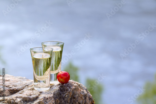 Two stacks of tequila with tomatoes are on rock by river