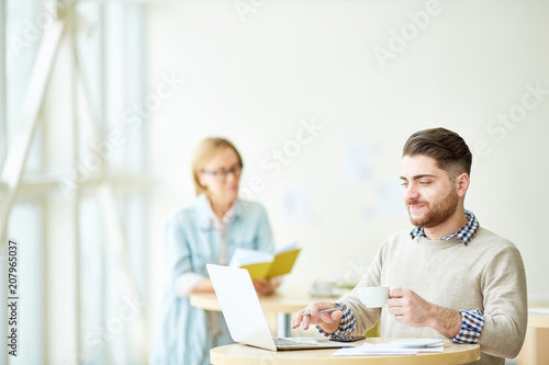 Young man enjoying cup of coffee and using laptop sitting in cafeteria with woman on background.