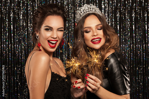 Leinwanddruck Bild Two beautiful young girls smile, laugh and hold the Bengal lights, meet Christmas and New Year. Clean skin and a hairstyle with bright lips. Photographed on a sparkling background.