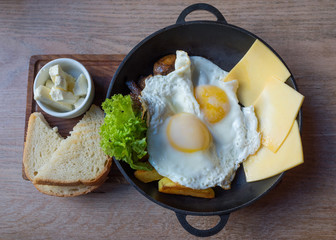 Breakfast, eggs, cheese, potatoes, butter, bread and salad in a frying pan on a wooden tray.