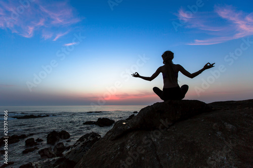 Fototapeta Yoga silhouette of a young woman practicing exercises on the ocean at sunset.