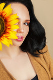portrait of a young woman with a sunflower