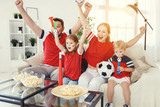 family of fans watching a football match on TV at home - 207987418