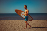 Young man with a surf board on the beach - 207989604