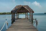 Muelle y choza de madera en un lago con  cielo azul - 207989881