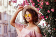 Leinwanddruck Bild - Outdoor close up portrait of young beautiful happy smiling curly girl wearing stylish yellow sunglasses, straw hat, pink top with ruffles. Model posing near blooming roses. Summer fashion concept