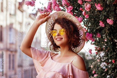Leinwanddruck Bild Outdoor close up portrait of young beautiful happy smiling curly girl wearing stylish yellow sunglasses, straw hat, pink top with ruffles. Model posing near blooming roses. Summer fashion concept