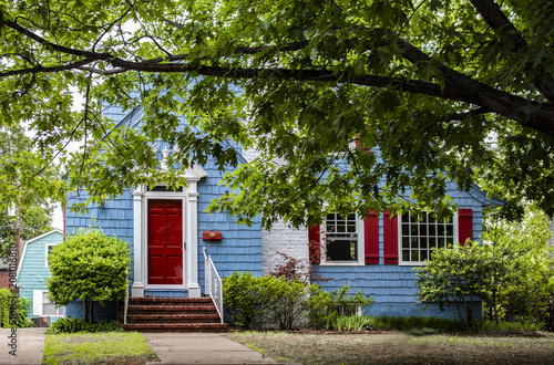 Cute brightly painted blue shingled cottage with red and white trim under a big tree
