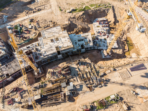 Fototapeta two cranes working on big construction site. aerial view