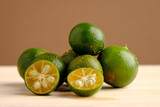 Calamansi on wooden table and brown background