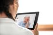 Leinwanddruck Bild - Diagnose und Sprechstunde über das Internet, Ärztin hält Tablet mit Patientin und Icons