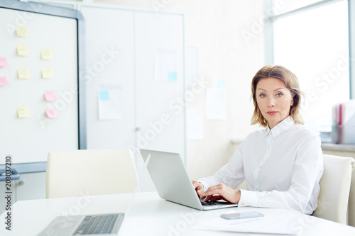 Portrait of confident mature businesswoman looking at camera while typing on laptop at office desk