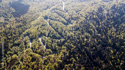 Plexiglas Zwart Winding road from high mountain pass, in spring time. Aerial view by drone . Romania
