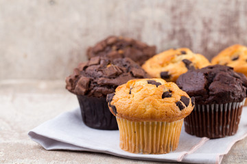 Homemade muffins with chocolate, vintage background.