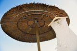 Wedding dress hung on a straw parasol on the beach - 208041435