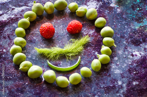 close up of symbol of smile made by vegetables and fruits on purple stone, copy space - 208043227