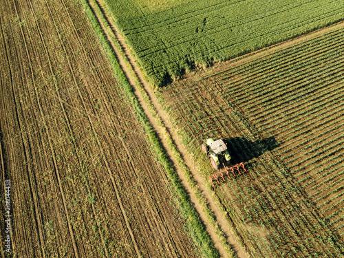 Fotobehang Trekker Tractor cultivating corn crop field, aerial view