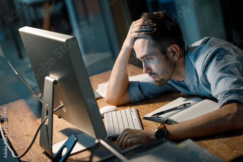 Young man leaning on hand looking extremely tired while finishing overtime project watching computer at table.