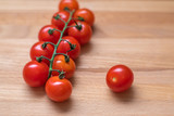 Branch and single cherry tomato on wooden table - 208048299