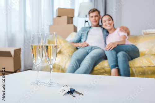 beautiful young couple relaxing on couch while moving into new home with champagne glasses and keys on foreground