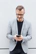 Leinwanddruck Bild - Mature man in grey jacket using mobile phone