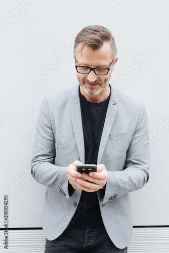 Leinwanddruck Bild Mature man in grey jacket using mobile phone