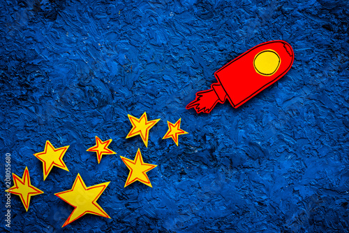 Space flight or space travel concept. Drawn stars and rocket or space shuttle on blue background top view copy space