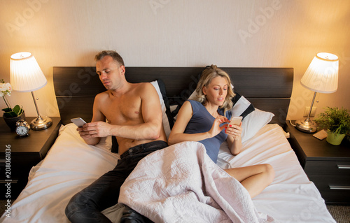 Couple in bedroom busy with their mobile phones