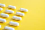 White pills on yellow background - 208065234